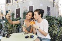 Itália, Pádua, duas jovens mulheres tomando selfie no café de calçada — Fotografia de Stock