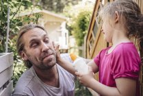Daughter applying sunscreen on father face in garden — Stock Photo