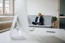 Donna d'affari seduta sul divano — Foto stock