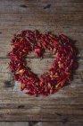 En forma de corazón con vainas de chile secas rojas en madera - foto de stock