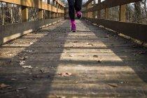 Close-up da mulher correndo na ponte de madeira — Fotografia de Stock