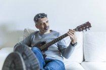 Ritratto di uomo maturo che suona la chitarra sul divano — Foto stock