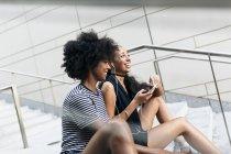 Deux amis assis sur les escaliers et l'écoute de musique avec des écouteurs et smartphone — Photo de stock