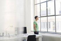 Молодой задумчивый бизнесмен смотрит в окно в кабинете — стоковое фото