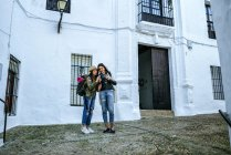 Молодые женщины-путешественницы смотрят фотографии в камеру на улице — стоковое фото