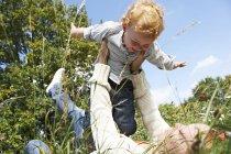 Mutter glücklich Sohn in Wiese anheben — Stockfoto