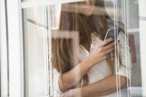 Женщина с мобильным телефоном у окна — стоковое фото