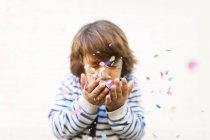 Portrait de garçon les yeux fermés soufflant des confettis des mains — Photo de stock