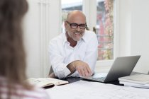 Empresário sorridente usando laptop no escritório — Fotografia de Stock