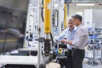 Hommes d'affaires, discuter dans le hall de l'usine — Photo de stock