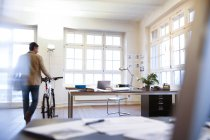Man with bicycle walking in modern informal office — Stock Photo