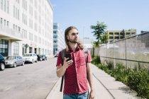 Portrait d'un homme adulte milieu, tenant le smartphone à rue — Photo de stock