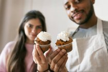 Retrato de jovem casal segurando muffins com chantilly — Fotografia de Stock
