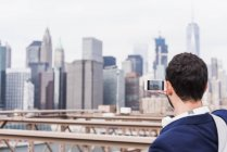USA, New York, Brooklyn bridge, Rear view of man taking photo of cityscape with smartphone — Stock Photo