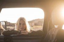 Retrato de jovem encostado na janela do carro e olhando para dentro — Fotografia de Stock