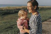 Mère avec petite fille debout sur la côte — Photo de stock