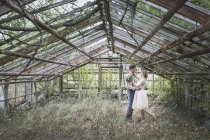 Bride and groom embracing in greenhouse — Stock Photo