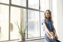 Lässige Geschäftsfrau hält Ordner im Büro — Stockfoto