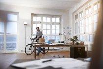 Mann mit Fahrrad zu Fuß in modernem informellen Büro — Stockfoto