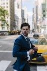 Ritratto di un uomo d'affari che attraversa la strada e guarda da parte — Foto stock