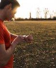 Ritagliate il ritratto di giovane uomo con smartwatch in campo — Foto stock