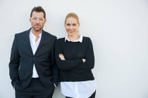 Портрет уверенного бизнесмена и женщины, стоящих напротив белой стены — стоковое фото