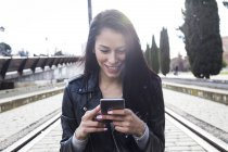 Portrait of smiling young woman wearing black leather jacket using cell phone — Stock Photo