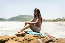 Portrait of smiling woman sitting on beach stone — Stock Photo