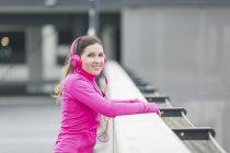 Frau im Kopfhörer im Freien auf der Brücke stehend — Stockfoto