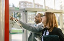 Young businessman and businesswoman looking at public transport timetable — Stock Photo