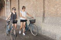 Two young women pushing bikes in city — Stock Photo