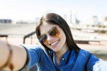 Woman wearing sunglasses taking selfie — Stock Photo