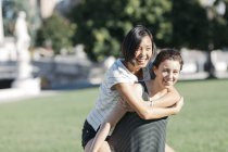 Young woman giving friend a piggyback ride in park — Stock Photo