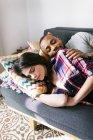 Retrato de jovem casal deitado no sofá — Fotografia de Stock