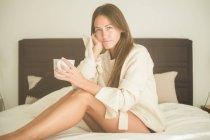 Mulher com xícara de café sentado na cama, olhando para a câmera — Fotografia de Stock