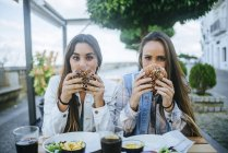 Two women holding hamburgers in front of their faces in cafe, Spain, Andalusia, Vejer de la Frontera — Stock Photo