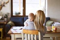 Мать с ребенком сидят дома за столом — стоковое фото