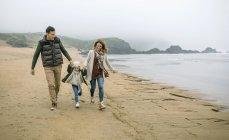 Spanien, asturias, lächelndes Paar spielt mit glücklichen Mädchen am Strand — Stockfoto