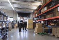 Geschäftsleute diskutieren in Fabrikhalle — Stockfoto