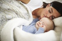 Close-up of Mother and baby sleeping head to head in bed — Stock Photo