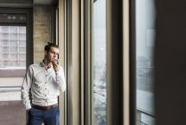 Portrait of young businessman using smartphone — Stock Photo