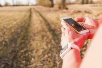 Ritagliate il ritratto di giovane uomo utilizzando smartphone nel campo — Foto stock