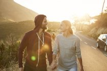 Happy young couple walking walking hand in hand at roadside — Stock Photo