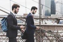США, Нью-Йорк, Бруклінський міст, двоє бізнесменів з смартфонів і навушниками ходити в місті — стокове фото