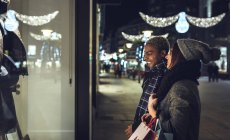 Young couple looking in shop window — Stock Photo