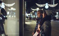 Молодая пара смотрит в витрину магазина — стоковое фото