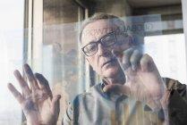 Retrato de hombre de negocios senior utilizando la pantalla de vidrio - foto de stock