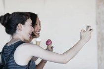 Dos mujeres jóvenes con conos de helado tomando selfie con smartphone - foto de stock
