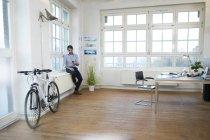 Mann mit Handy in einem modernen informellen Büro — Stockfoto