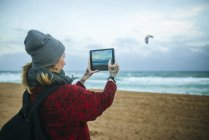 Tattooed woman taking a photo with tablet on the beach, Spain, Catalonia, Barcelona — Stock Photo